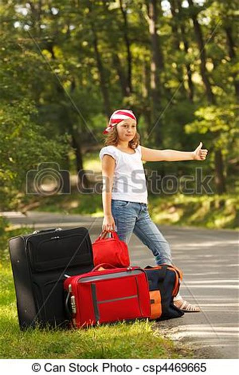 Young hitch-hiker girl standing on road side afternoon in